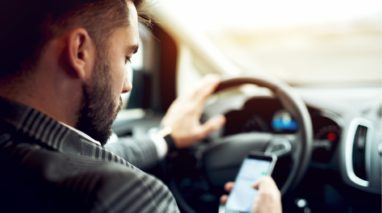Man driving and looking at his smarthphone