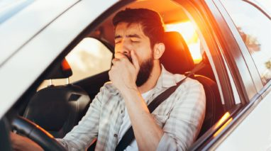 photo of man yawning while driving tried