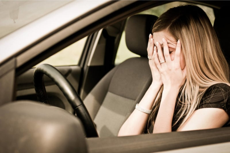 young woman in car upset as excluded driver