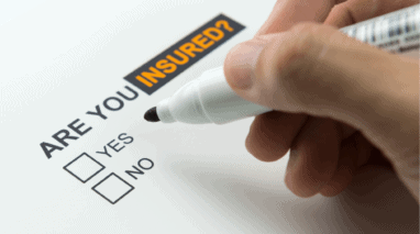 Hand with marker over a sheet of paper that says are you insured? with a yes or no option