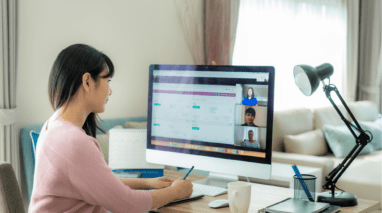 Woman having a video conference on her desktop computer in her home