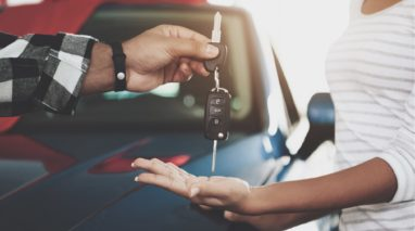young man handing over the keys to his car to his friend