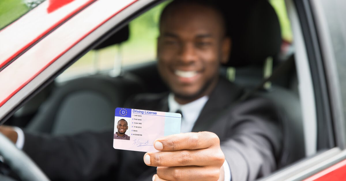 Smiling man sitting on his car holding up his drivers license