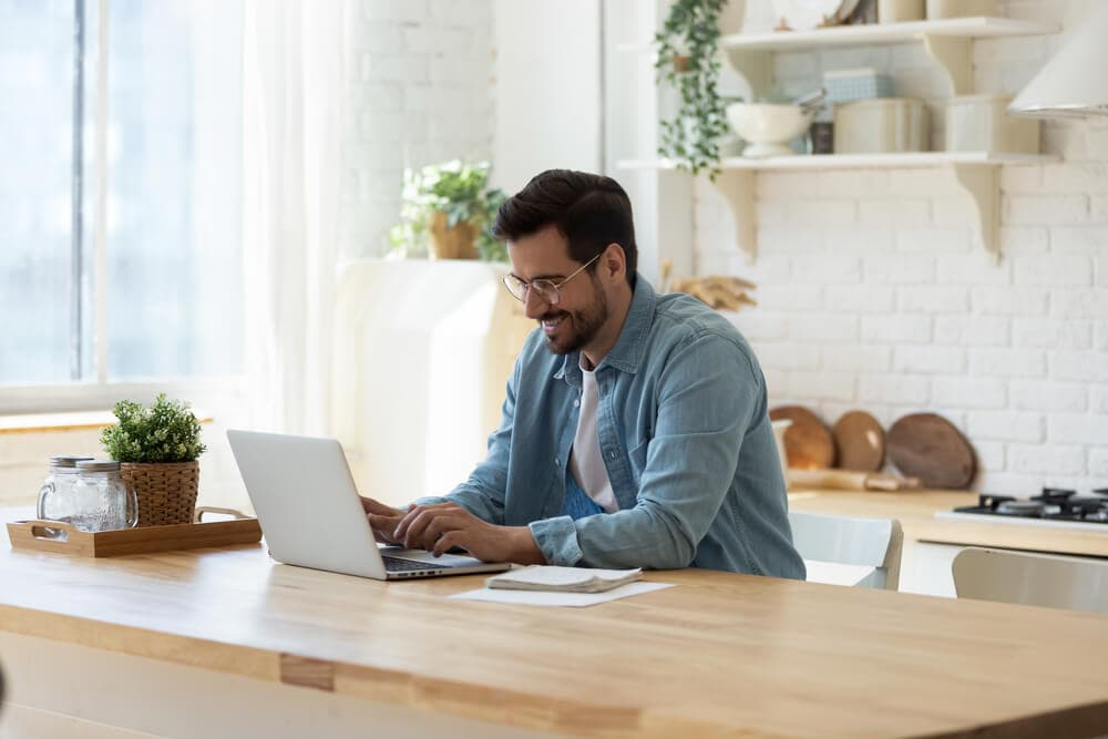 happy young car insurance agent with laptop offering online services