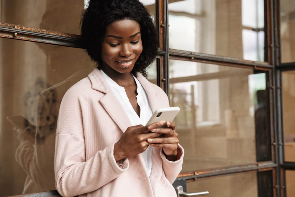 smiling young african american woman looking at smartphone