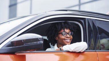 smiling young african american woman in drivers seat of car looking out the window