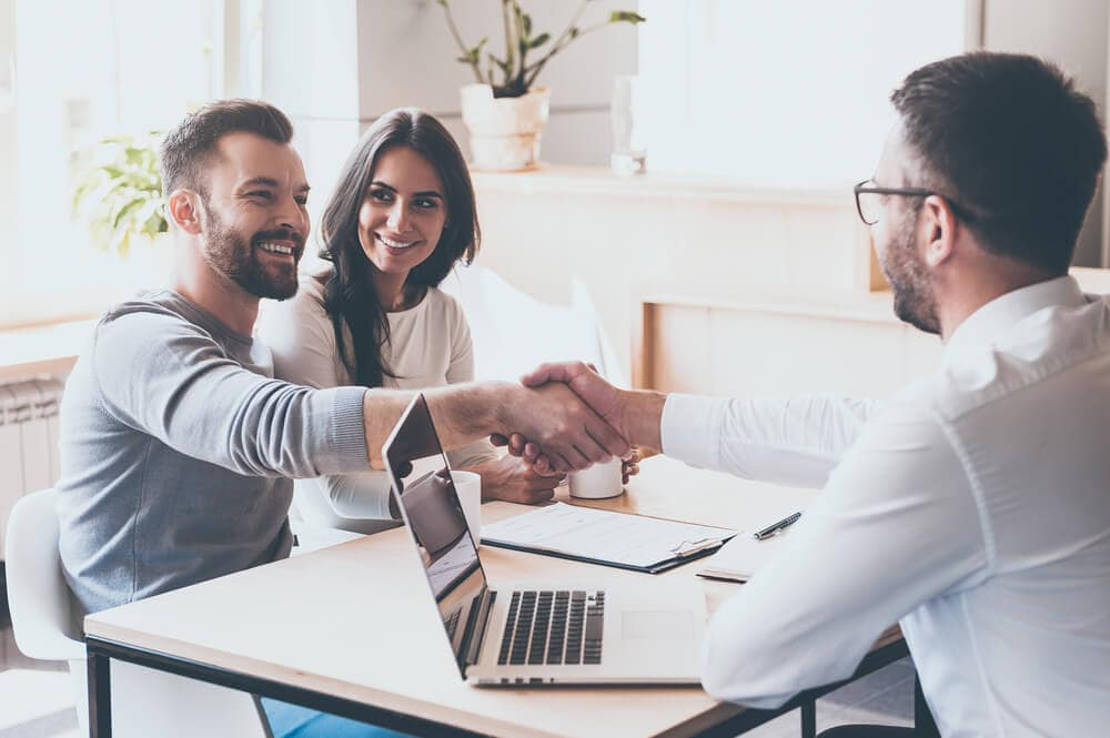 happy couple with insurance agent shaking hands