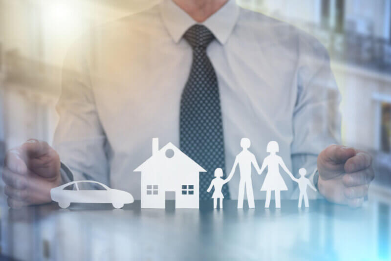 Insurer protecting a family, a house and a car with his hands